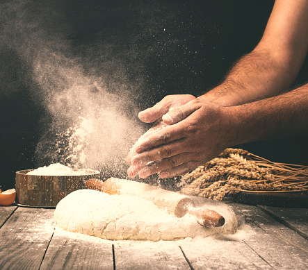 Man preparing bread dough on wooden table in a bakery 602313128