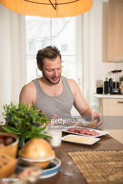 Man preparing breakfast in the kitchen, Munich, Bavaria, Germany