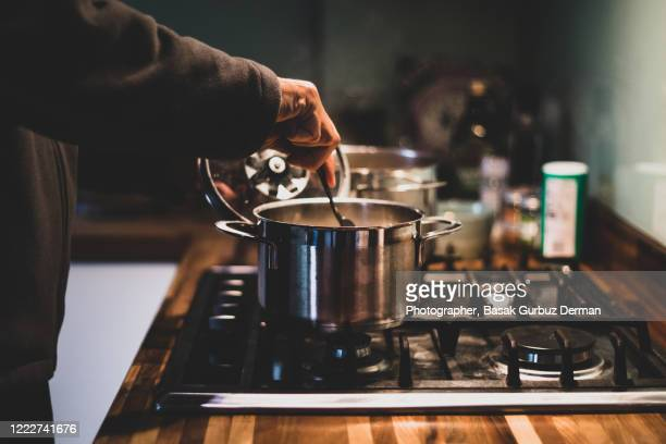 a man preparing dinner - cooking pan stock pictures, royalty-free photos & images