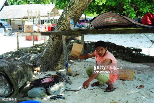 man preparing fish on barbecue Pulau Weh Sumatra Indonesia