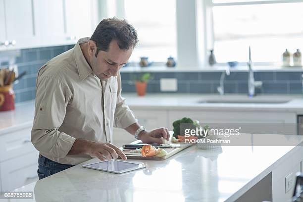 Man preparing food and looking at digital tablet in kitchen