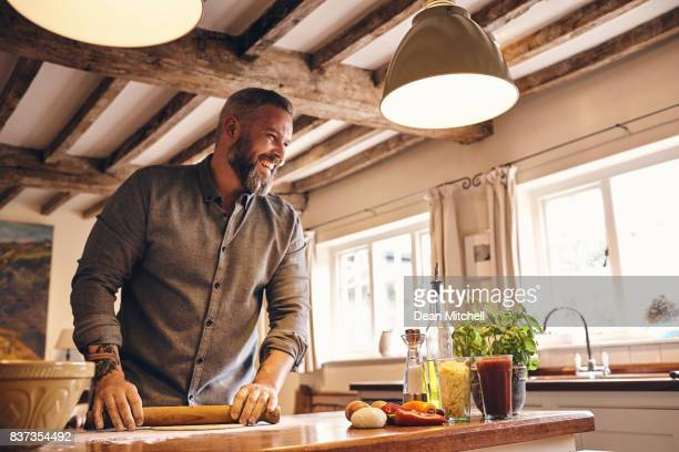 man preparing food at home - dean foods stock photos and pictures