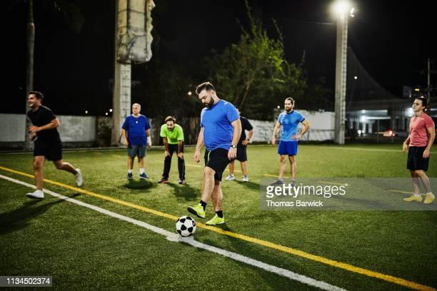 man preparing for penalty kick during evening soccer match with friends - strafstoß serie fußball und andere sportarten stock-fotos und bilder