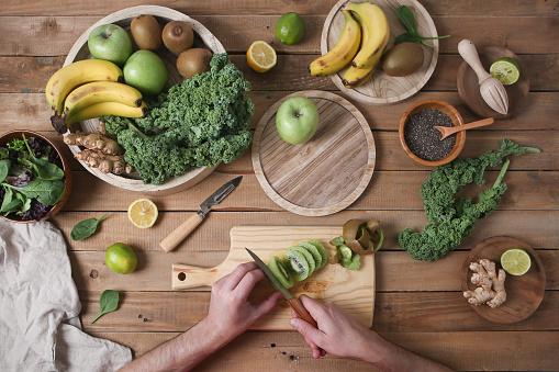 Man preparing green smoothie slicing kiwi - gettyimageskorea