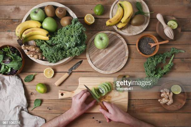 man preparing green smoothie slicing kiwi - detox stock pictures, royalty-free photos & images