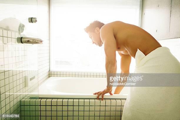 Hombre preparando su baño en el baño moderno