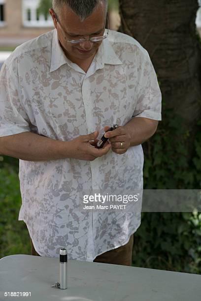man preparing his e-cigarette - jean marc payet photos et images de collection