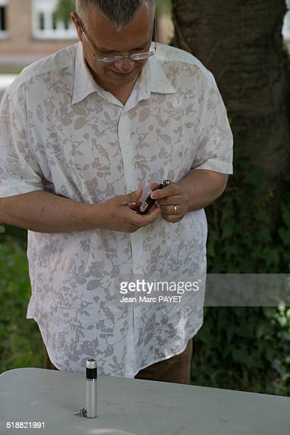man preparing his e-cigarette - jean marc payet stockfoto's en -beelden