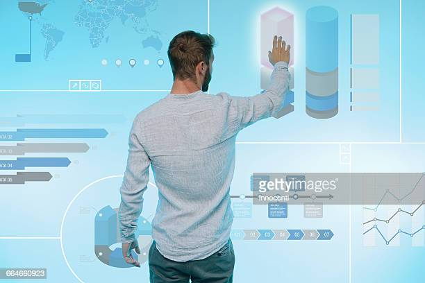 man preparing presentation on graphical screen, rear view - touch sensitive stock pictures, royalty-free photos & images