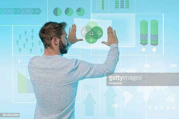 Man preparing presentation on graphical screen, rear view