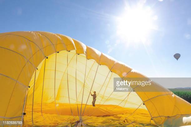 man preparing the yellow envelope of a hot air balloon for take off - yellow stock pictures, royalty-free photos & images