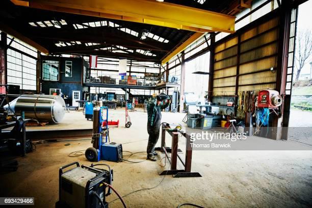 Man preparing to cut piece of metal in workshop