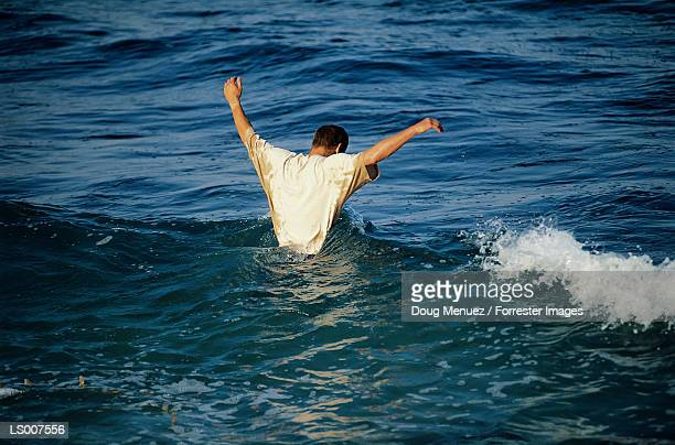man preparing to dive under - waist deep in water stock pictures, royalty-free photos & images