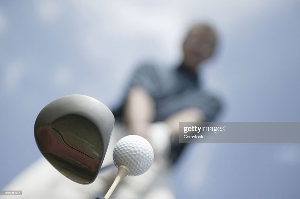 Man preparing to hit golf ball : Stock Photo