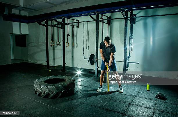 Man preparing to hit tire with sledgehammer
