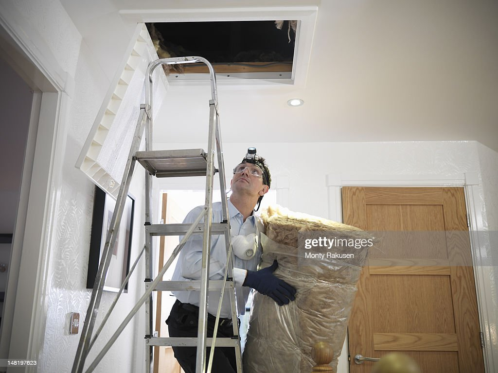 Man preparing to insulate loft in house : Stock Photo