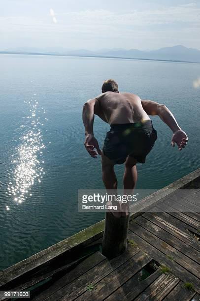 man preparing to jump into lake, rerar view - beugen oder biegen stock-fotos und bilder