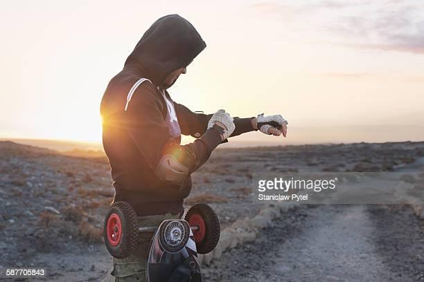 Man preparing to landboarding at sunrise