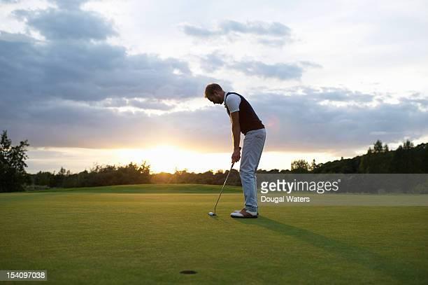 Man preparing to putt golf ball at sunset.