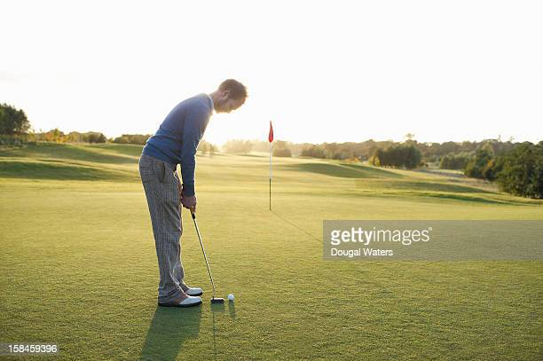 man preparing to putt golf ball on green. - golf flag stock photos and pictures