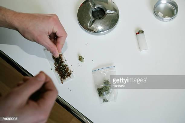 Man preparing to roll a marijuana joint