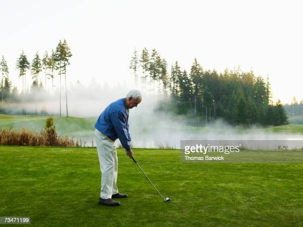 man preparing to tee off on golf course, side view - golpear desde el tee fotografías e imágenes de stock