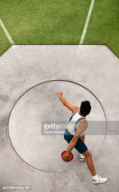 Man preparing to throw discus at track, elevated view