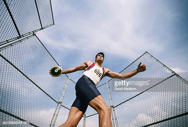 Man preparing to throw discus at track, low angle view