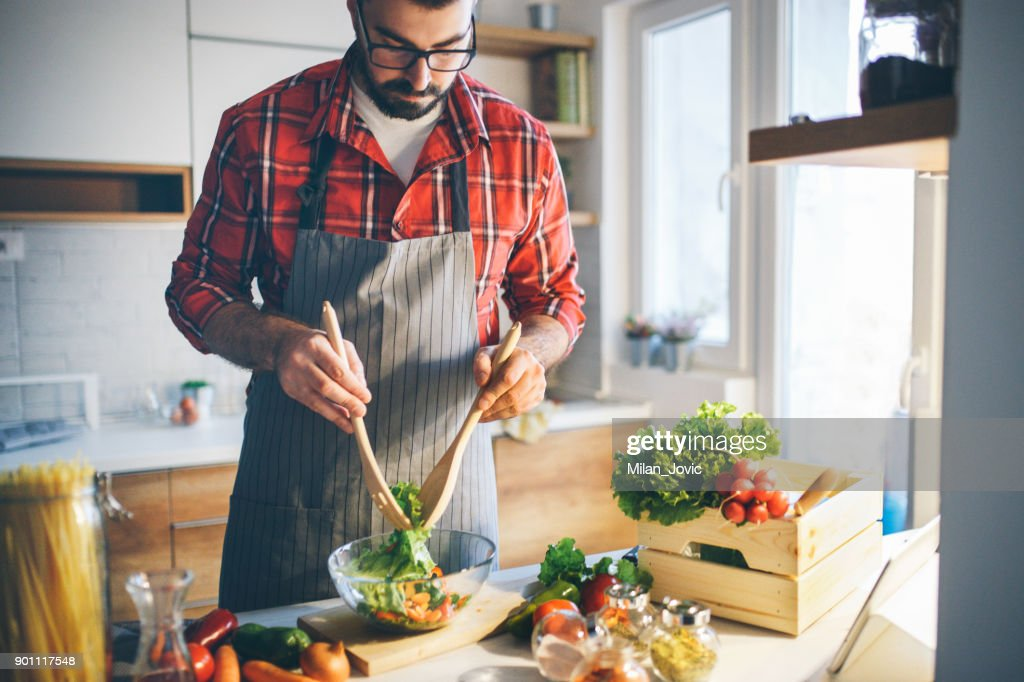 Man preparing vegetable salad at home : Stock Photo