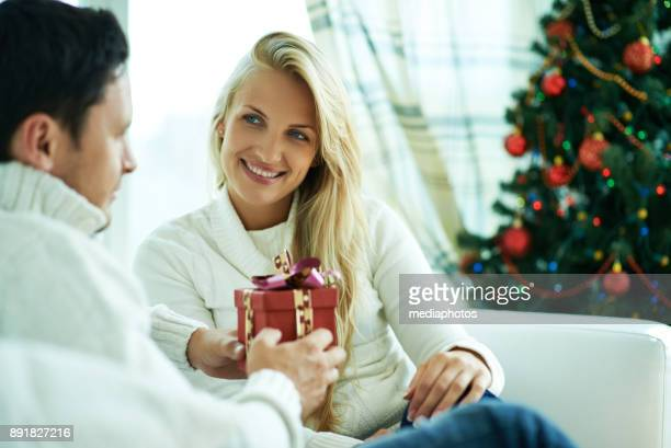 Man presenting Christmas gift to girlfriend