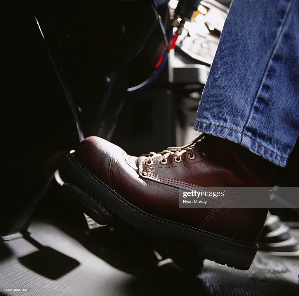 Man pressing car pedal, close-up, low section : Stock Photo