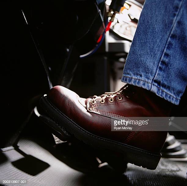 Man pressing car pedal, close-up, low section