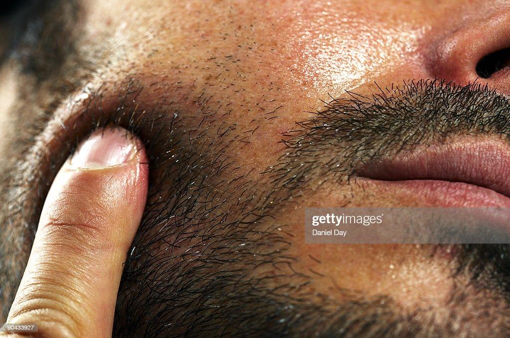 Man pressing finger against cheek : Stock Photo