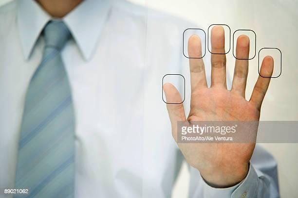 Man pressing fingertips to fingerprint reader