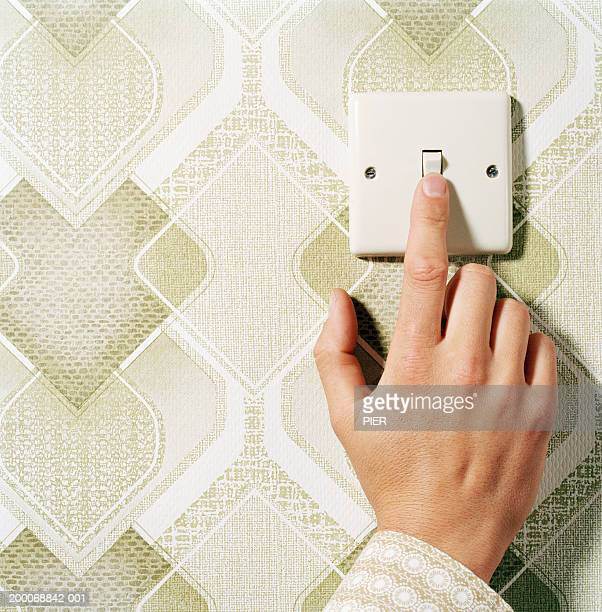Man pressing light switch on patterned wall, close-up