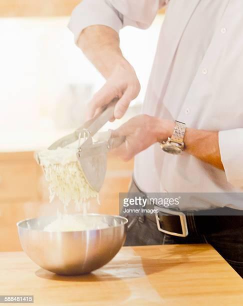 Man pressing potatoes through potato ricer