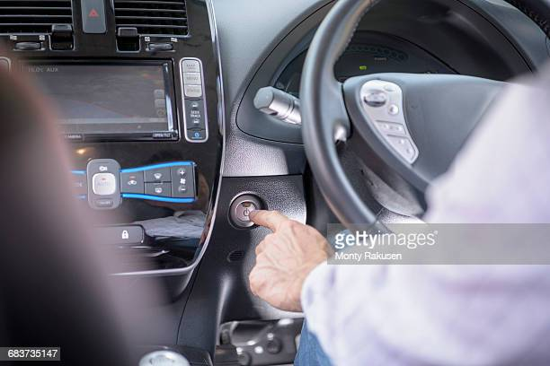 Man pressing start button on electric car, close up