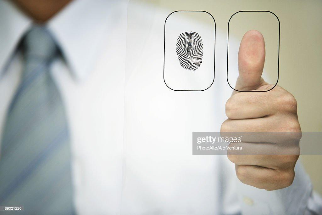Man pressing thumb to fingerprint reader : Stock Photo