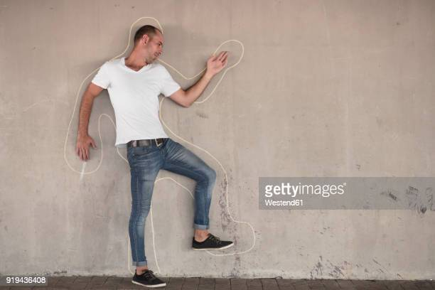 Man pretending to be dead standing with chalk outline drawn on concrete wall