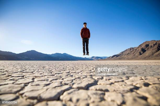 a man pretending to levitate in the desert. - lake bed stock pictures, royalty-free photos & images