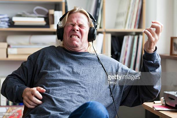 man pretends to play guitar listening to music - rock stock pictures, royalty-free photos & images