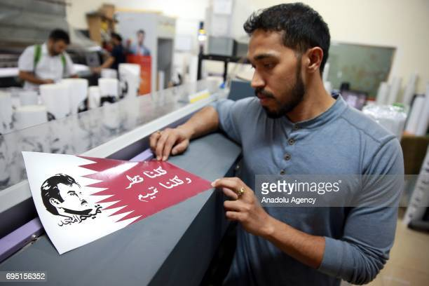 A man prints a poster of Emir of Qatar Sheikh Tamim bin Hamad Al Thani at a printing house in Doha Qatar on June 12 2017 People in Qatar hang posters...