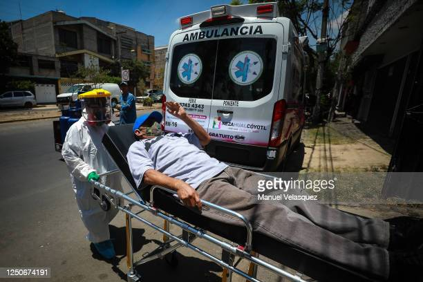 A man probable COVID19 waves goodbye to his wife as Antonia paramedic of Nezahualcoyotl transports him to an ambulance to be taken to a hospital...