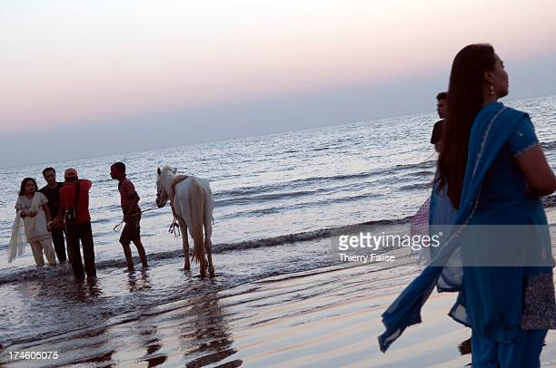 COX'S BAZAR BANGLADESH A man proposes a horse to rent for a ride on the Cox's Bazar beach