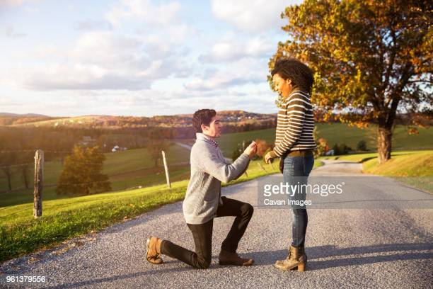 man proposing surprised girlfriend on footpath - engagement stock pictures, royalty-free photos & images