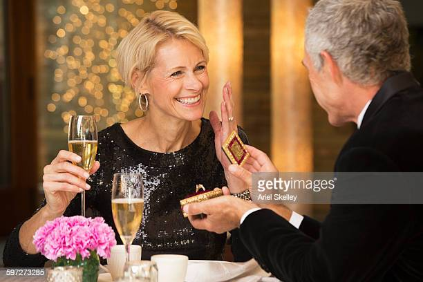man proposing to girlfriend at dinner - man holding engagement ring stock photos and pictures