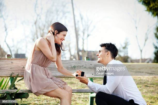 man proposing to girlfriend at park - fidanzato foto e immagini stock
