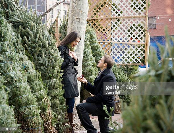 man proposing to girlfriend on christmas tree lot - pop up store stock pictures, royalty-free photos & images