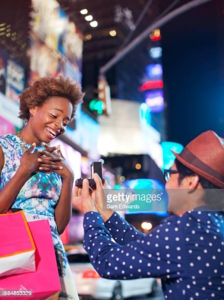 Man proposing to girlfriend on city street