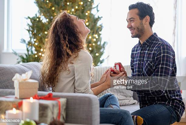 man proposing to girlfriend on sofa - engagement ring box stock photos and pictures